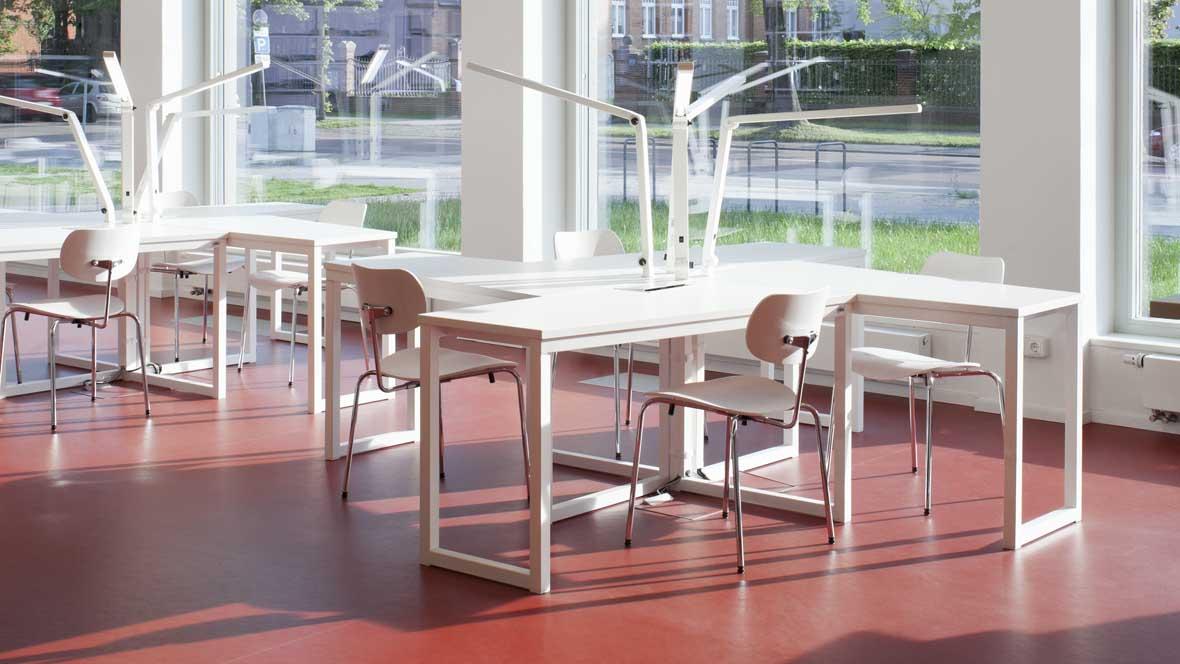 Neue Bibliotheken im Bauhaus Dessau Weiße Tische und Stühle auf rotem Boden  – Forbo Marmoleum Walton