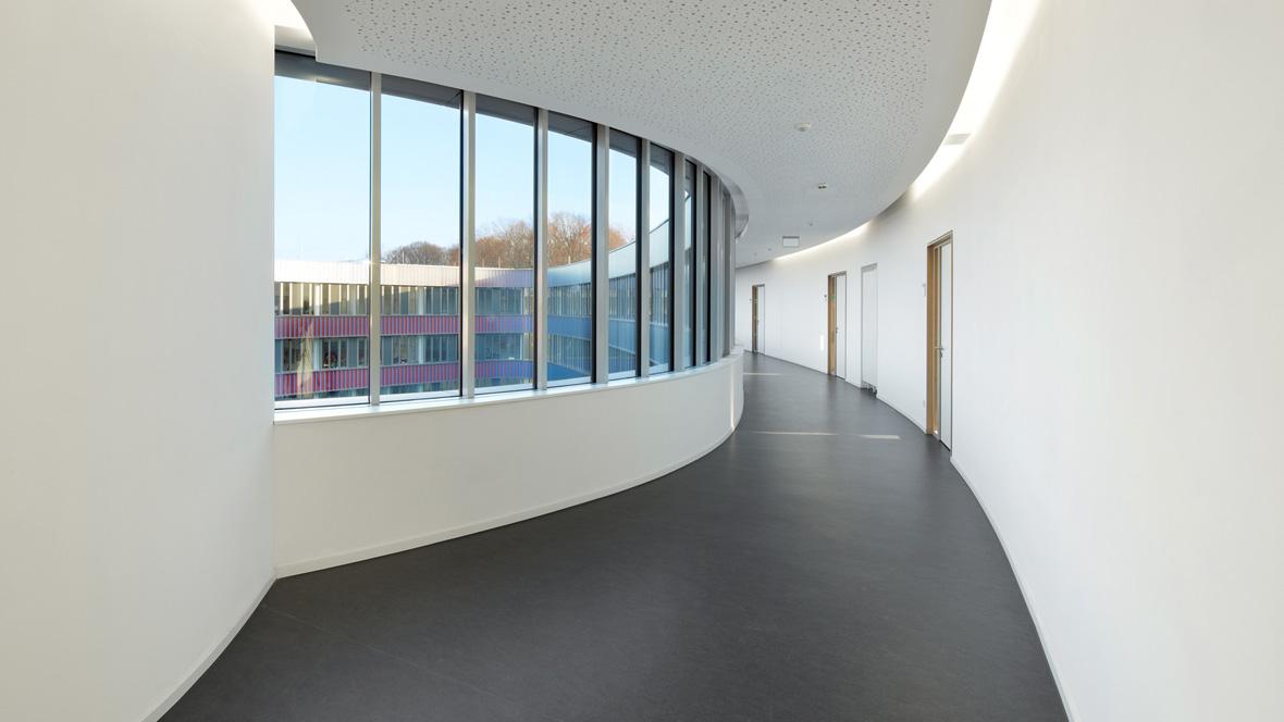 Neues Gymnasium Bochum Weißer Gang mit Fensterfront und grau abgesetztem Boden – Forbo Marmoleum Fresco