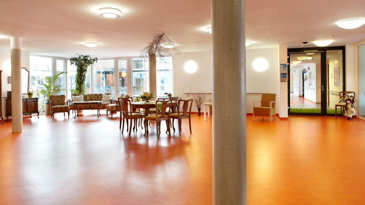 """Neubau Seniorenanlage """"Heidehof"""" Hattingen Alte Holzstühle und Tische auf orangenem Boden – Forbo Marmoleum Fresco"""