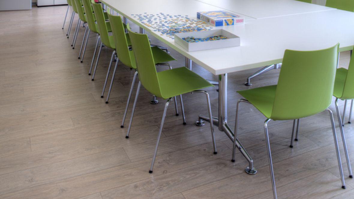 Lebenshilfe Magdeburg Konferenztisch mit grünen Stühlen – Forbo Allura Wood