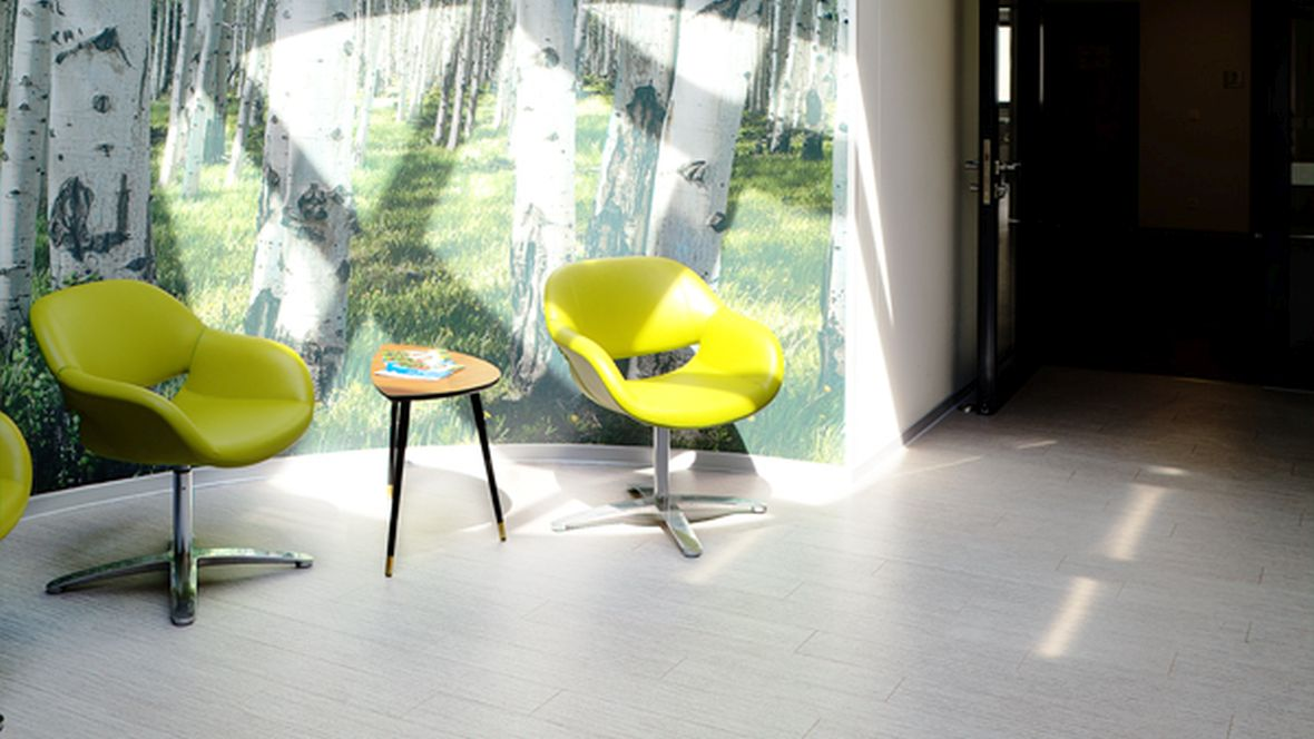 Lebenshilfe Magdeburg Stühle vor Wand mit Motivtapete – Forbo Allura Wood