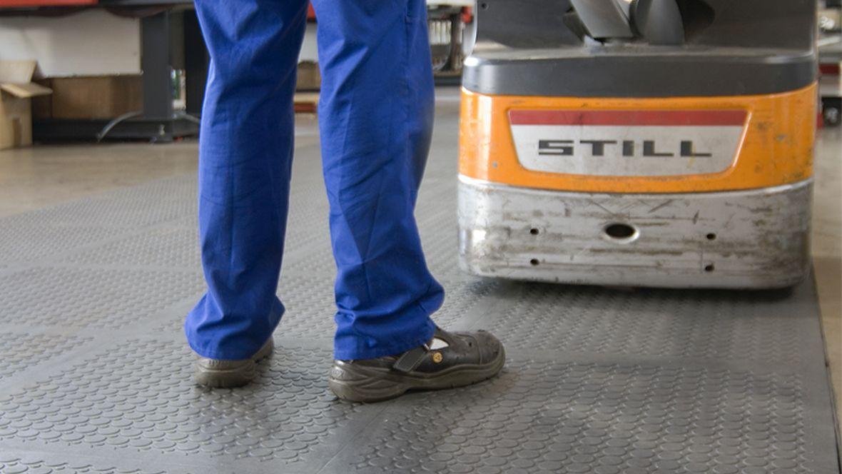 Playmobil Zirndorf Nahaufnahme Person steht mit Arbeitsschuhen auf rutschfesten Boden– Forbo R11 Plus