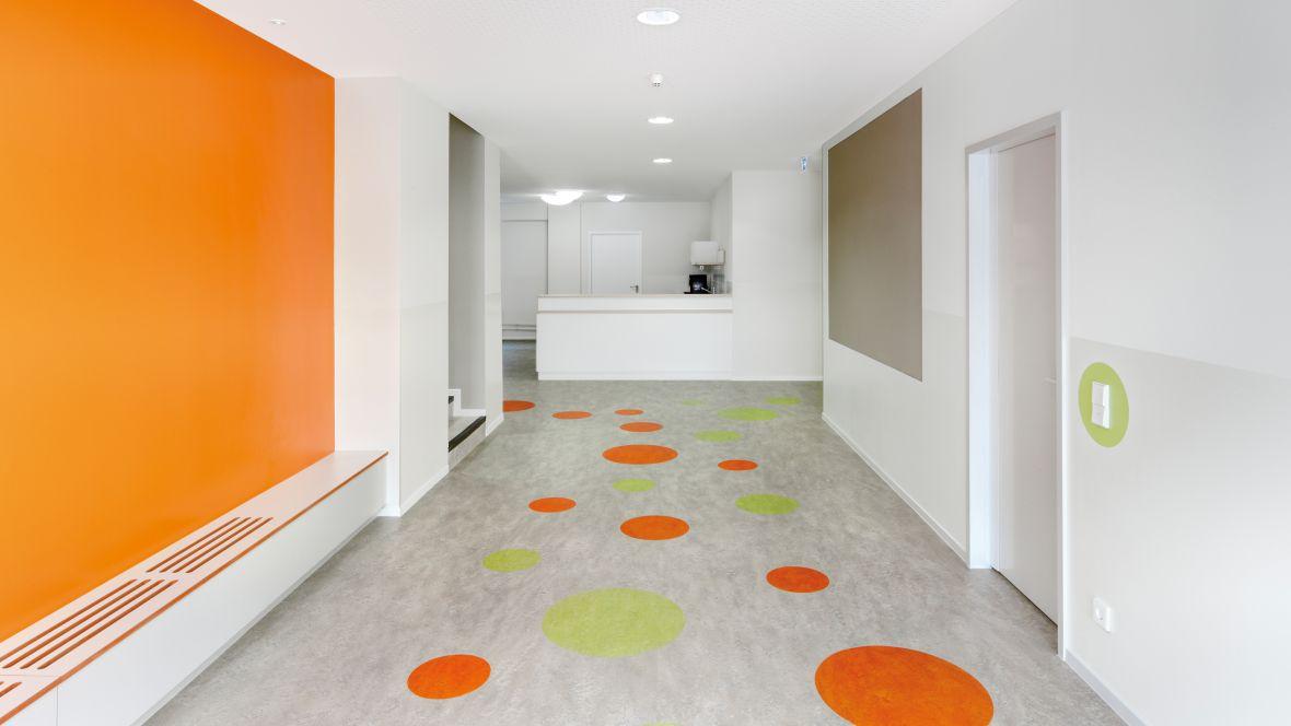 KiTa Elbpiraten Hamburg Runde farbige Intarsien im grauen Bodenbelag – Forbo Marmoleum Real