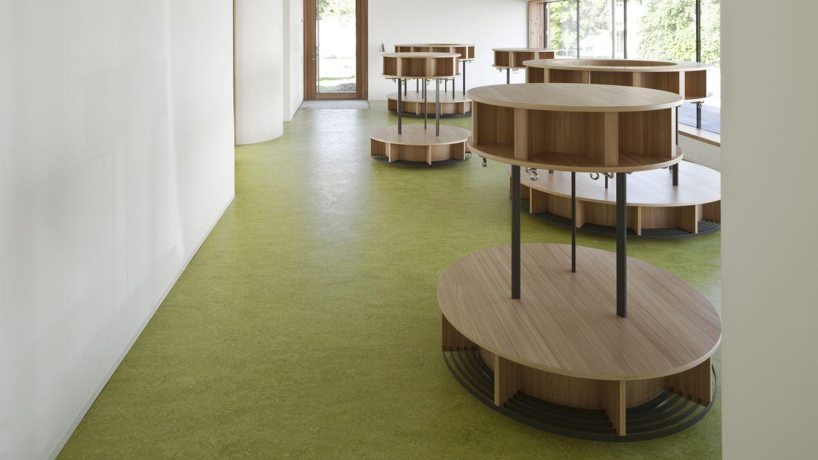 Caritas Kindergarten St. Peter und Paul Landshut Runde Garderobe aus Holz auf grünem Linoleumboden – Forbo Marmoleum Decibel