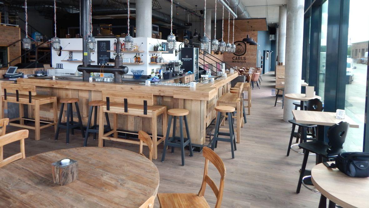 Carls-Wirtshaus Karlsruhe Rastraum mit Tischen und Stühlen – Forbo Allura Wood