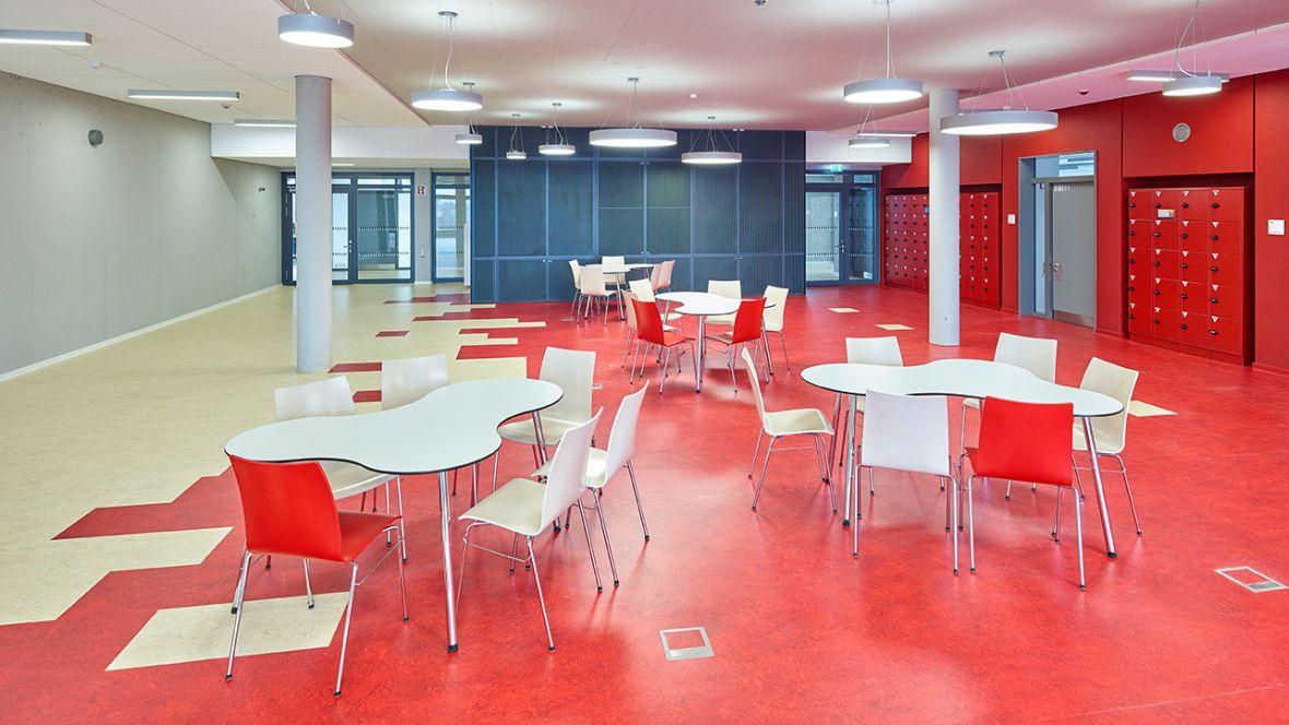 Wilhelm-Bracke Gesamtschule Braunschweig Weiße Stühle auf rotem Boden – Forbo Marmoleum Real