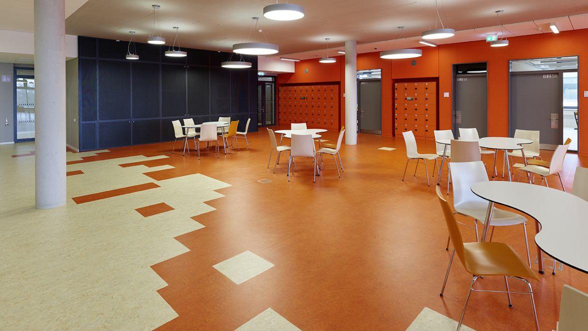 Wilhelm-Bracke Gesamtschule Braunschweig Weiße Stühle auf orangenem Boden – Forbo Marmoleum Real