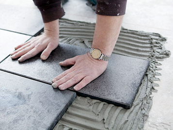 Hands laying tiles with Forbo Eurocol cement-based construction adhesive for tiles.