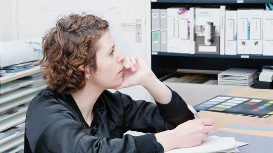 Forbo Mitarbeiterin am Arbeitsplatz mit Stift in der Hand am Nachdenken. Im Hintergrund Farbpaletten von Forbo Bodenbelägen.