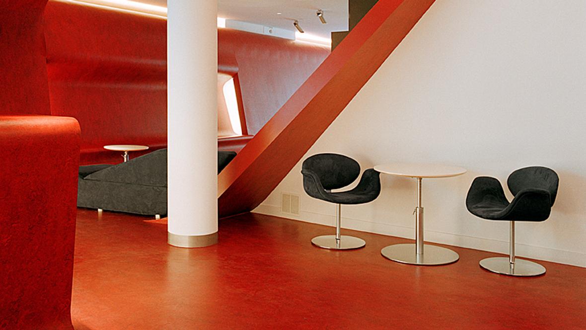 Hotel Q Berlin Stühle und Tisch auf rotem Boden – Forbo Marmoleum Real