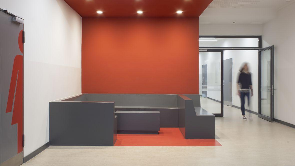 BBS Handel Hannover Flur mit grauem Boden und rot-zoniertem Sitzbereich – Forbo Marmoleum Fresco