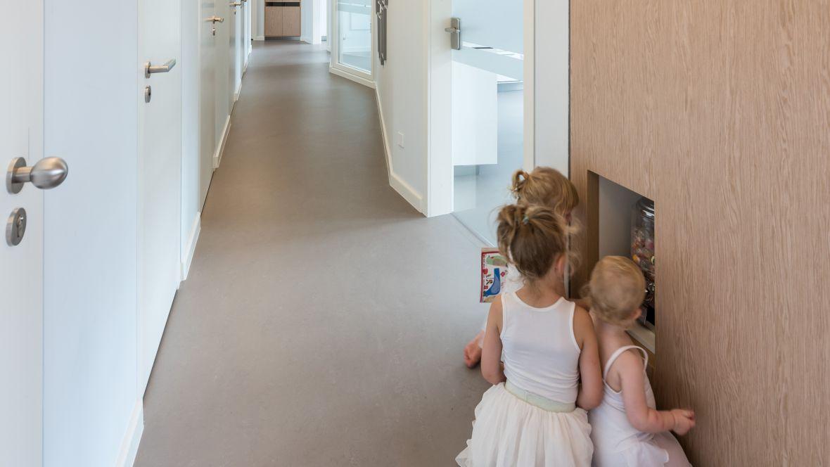 Zahnarztpraxis Kleene Große Zähne Berlin Steglitz Kinder im Gang – Forbo Marmoleum Concrete