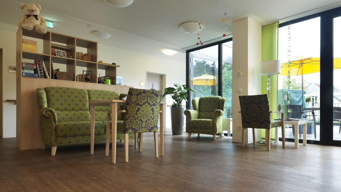 Ferdinand-Heye-Haus Düsseldorf Aufenthaltsraum mit grünen Sesseln – Forbo Allura Wood