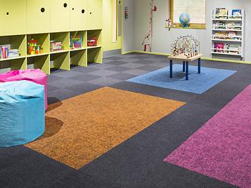 Flotex, der waschbare Textilboden, in Fliesenformat in einem Kindergarten. Eine Produktlinie, die seit der Akquisition von Bonar Floors im Jahr 2008 das Produktportfolio von Forbo ergänzt.