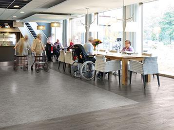 Alterspflege und sozialer Wohnungsbau: Stühle und Tische in einem Altersheim mit LVT Boden (Forbo Allura Luxury Vinyl Tiles).