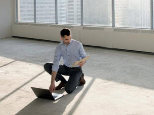 man op betonvloer in leeg gebouw