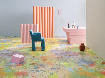 kleurrijke tie dye losleg vinylvloer met blauwe stoel en roze tafel